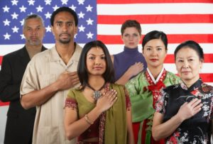 adults in traditional dress from around the world standing in front of a large U.S. flag with hands over hearts