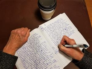 The hands of a writer working in a notebook. A cup of coffee in the backgroud.