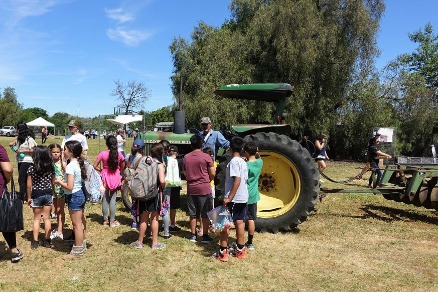 man with tractor speaks to group of students
